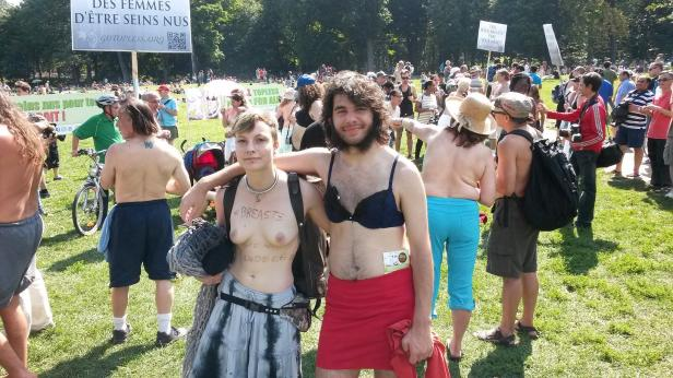 A young couple show their support for women's rights to be topless on Sunday, Aug. 24 at Mont-Royal park in Montreal.