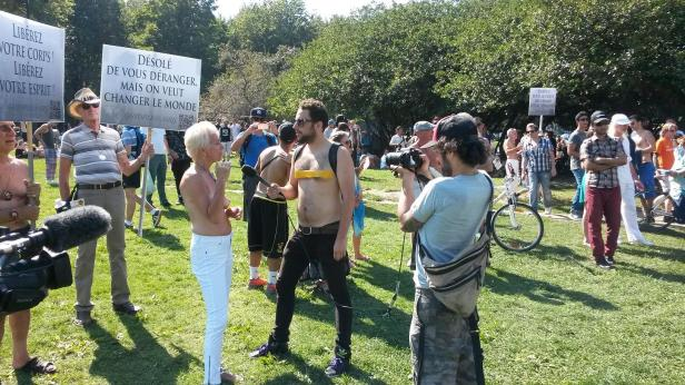 Sylvie Chabot is interviewed by a media person who shows his support by taping over his breasts at Sunday's demonstration in support of women's rights to be topless in public. (Photo by Jillian Page exclusively for jillianpage.com. No other reproduction permitted.)